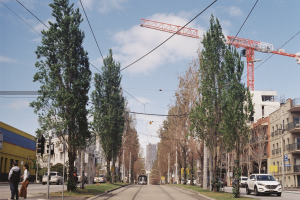 Image shows a typical inner Melbourne neighbourhood with tramtracks and overhead wires, trees, vehicles, people, buildings, and construction crane